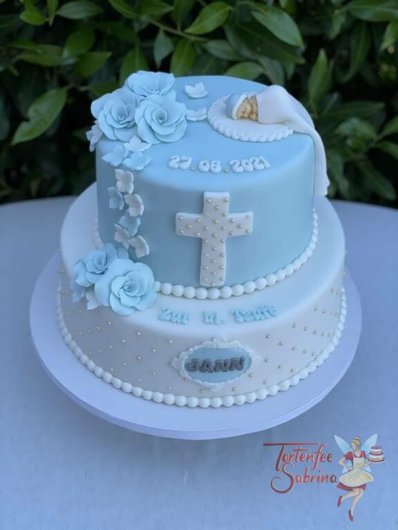 Tauftorte - Kreuz mit Zuckerperlen und süßem Baby unter der weißen Decke, ebenso auf der Torte sind blaue Rosen.