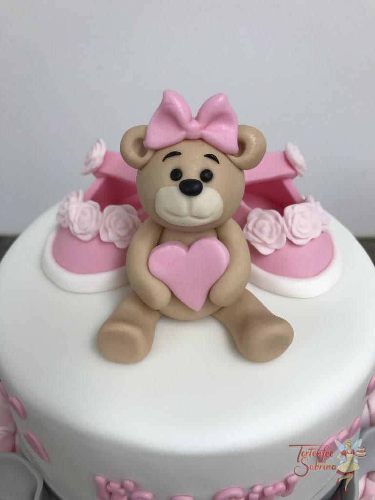 Babytorte - Bärchen mit Herz, sitzt auf einer 2-stöckigen Torte verziert mit Schleife, Schüchen und Rüschen.