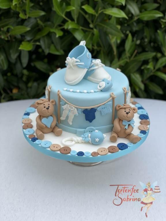 Babytorte - Bärchen mit Knöpfen und einer Wäscheleine mit Babykleidung, ebenfalls auf der Torte Babyschüchen.
