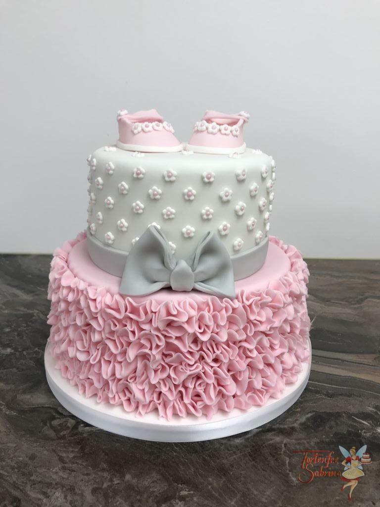 Babytorte - Rosa Schüchen mit Rüschen. Die Torte wurde aufwendig mit Rüschen und Blümchen verziert. Als Abschluss der Torte ist eine grau Schleife.