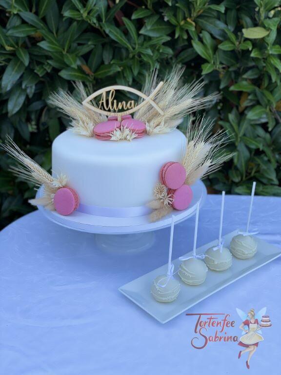 Erstkommunionstorte - Makronen und Ähren zieren die Torte, ganz oben ein Cake Topper in der Form eines Fisches.
