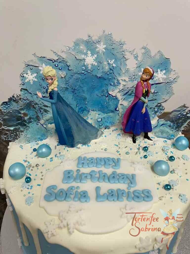 Geburtstagstorte Mädchen - Anna und Elsa in der Eiswelt sind hier auf der Torte zu sehen, ein weißer Drip ziert ebenso die Torte.