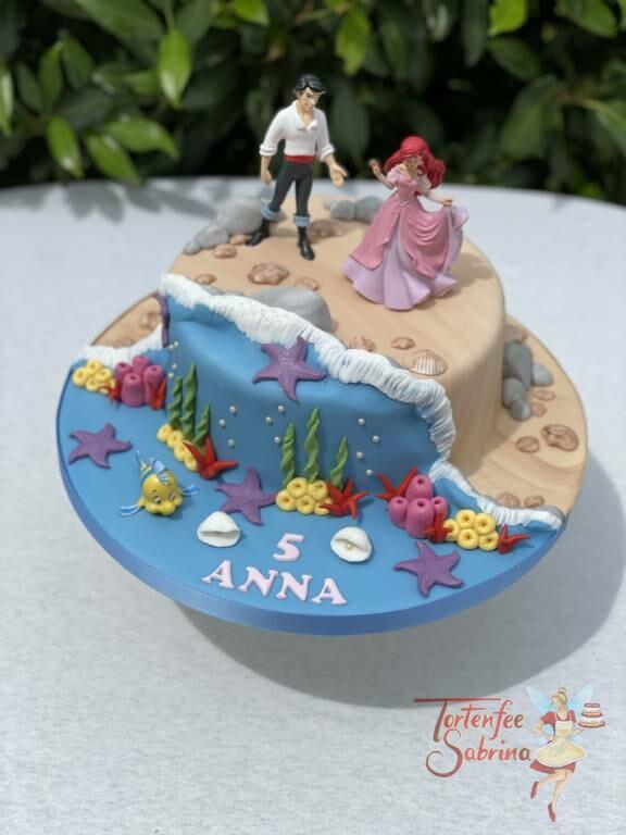Geburtstagstorte Mädchen - Arielle und das Meer, steht mir Eric am Strand vor einer kleine sanften Welle aus dem Meer.