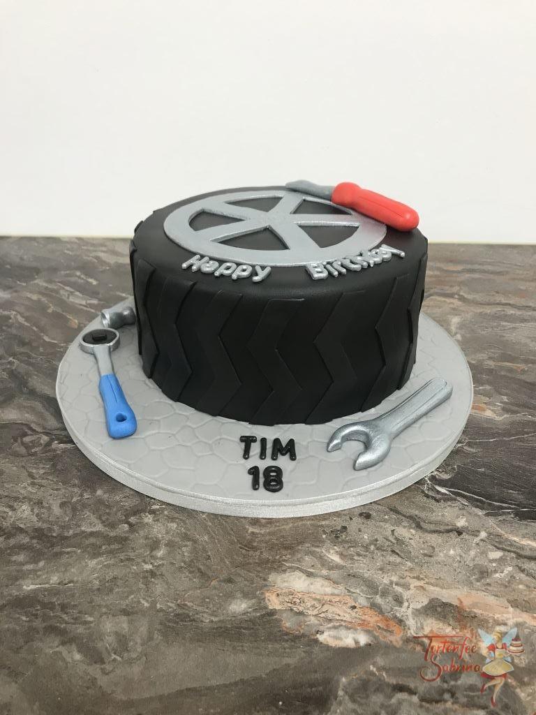 Geburtstagstorte Erwachsene - Autoreifen mit silberner Felge und verschiedenem Werkzeug Schraubenschlüssel und Ratsche.