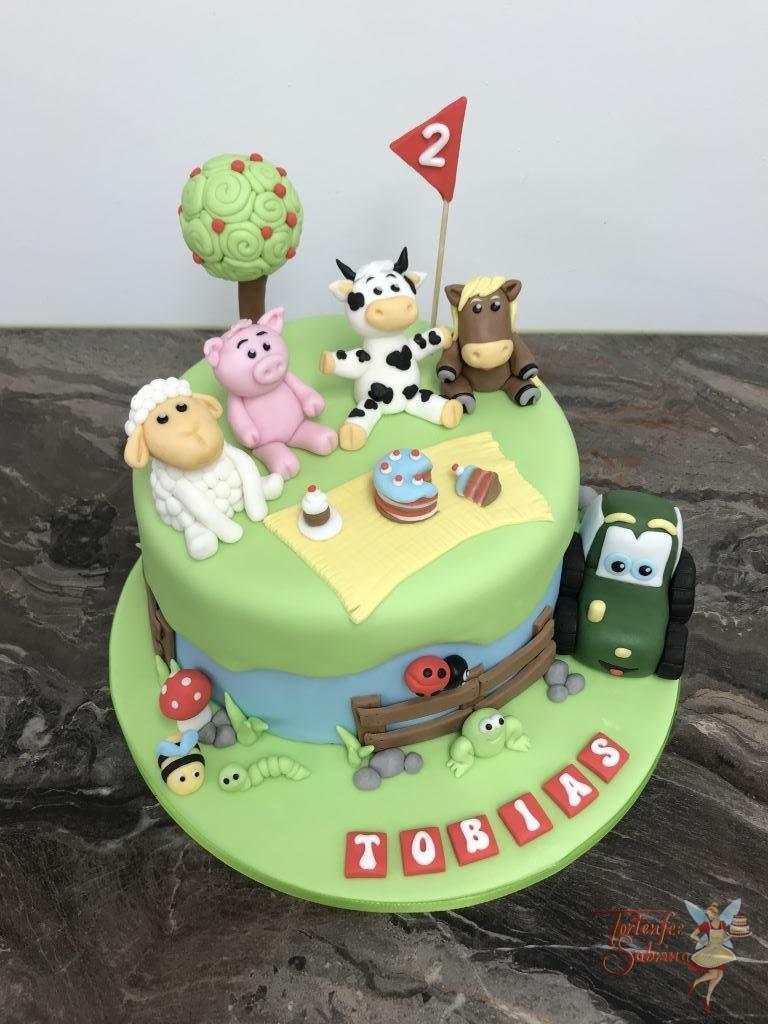 Geburtstagstorte Buben - Bauernhoftiere auf der Wiese, sitzen vergnügt rund um eine Decke mit Leckereien. Ebenfalls auf der Torte ist ein Traktor.