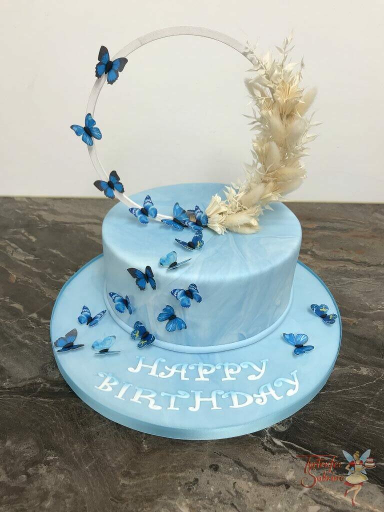 Geburtstagstorte Erwachsene - Blaue Schmetterlinge mit Trockenbumen auf weißen Ring, krönen die blau marmorierte Torte.