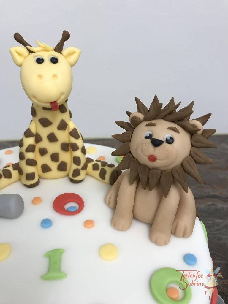Geburtstagstorte Buben - Bunte Tierwelt, hier sind ein Elefant, eine Giraffe und ein Löwe sitzend auf der Torte und mit bunten Kugeln und Kreisen verziert.