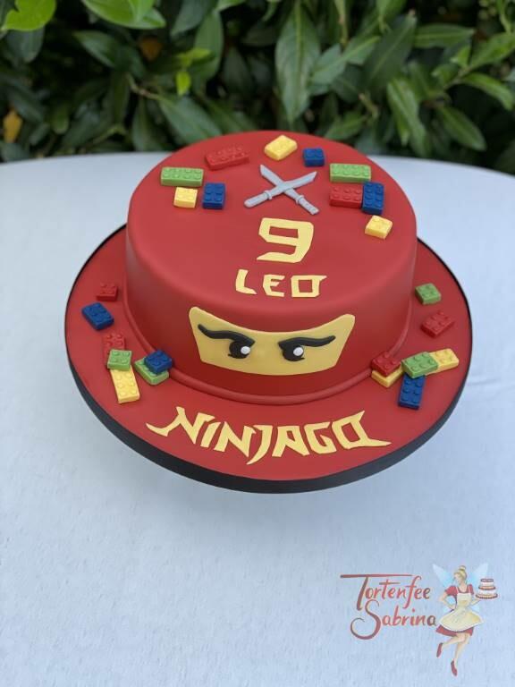 Geburtstagstorte Buben - Der rote Ninjago mit einem schönen Schirftzug in gelb und vielen bunten Leogsteinen.