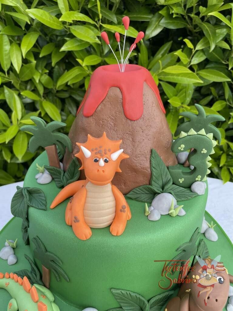 Geburtstagstorte Buben -Dinos beim Vuklan der gefährlich seine Lava über sich verteilt, darunter sitzen 3 freundliche Dinosaurier.