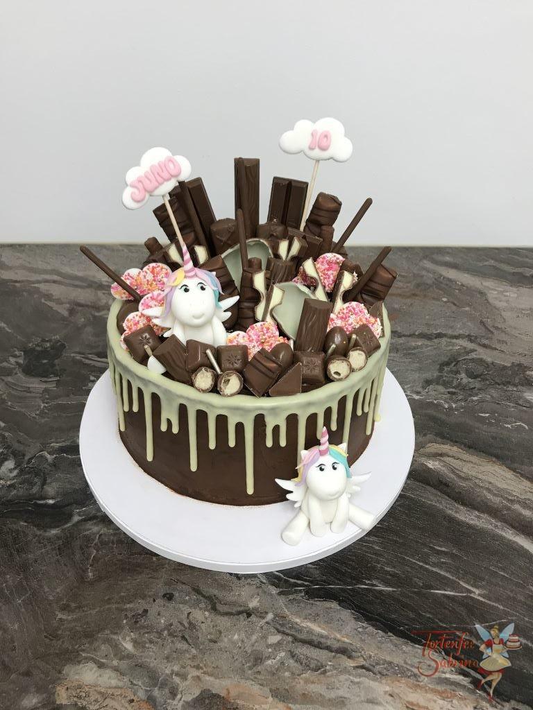 Geburtstagstorte Mädchen - Einhorn im Drip versteckt und schaut zwischen den leckersten Süßigkeiten hervor.