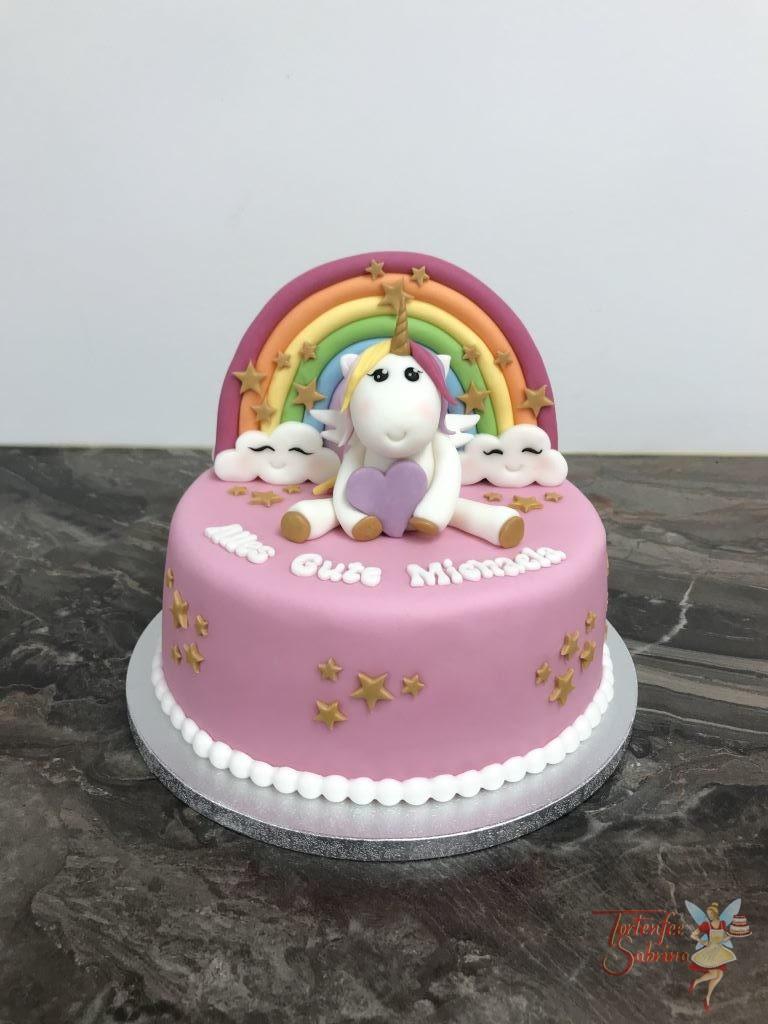 Geburtstagstorte Mädchen - Einhorn mit Regenbogen und Sternen. Das Einhorn hat auch bunte Haare und ein lila Herz in der Hand.