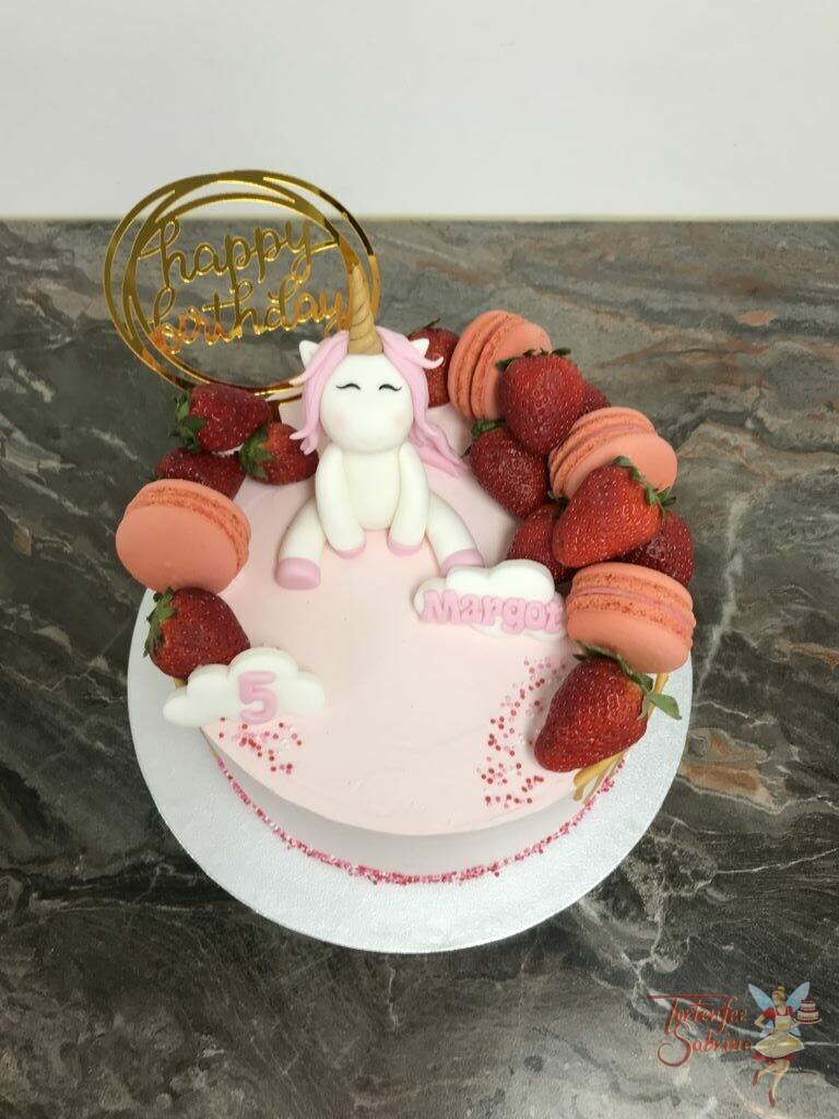 Geburtstagstorte Mädchen - Einhorn zwischen Früchten und Süßem, sitzt oben auf der Torte welche mit einem goldenem Drip und Cake Topper verziert wurde.