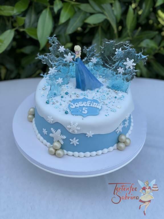Geburtstagstorte Mädchen - Elsa und die Eiskristalle in mitten der weißen Schneedecke und Schneeflocken mit glitzernden Zuckerperlen.