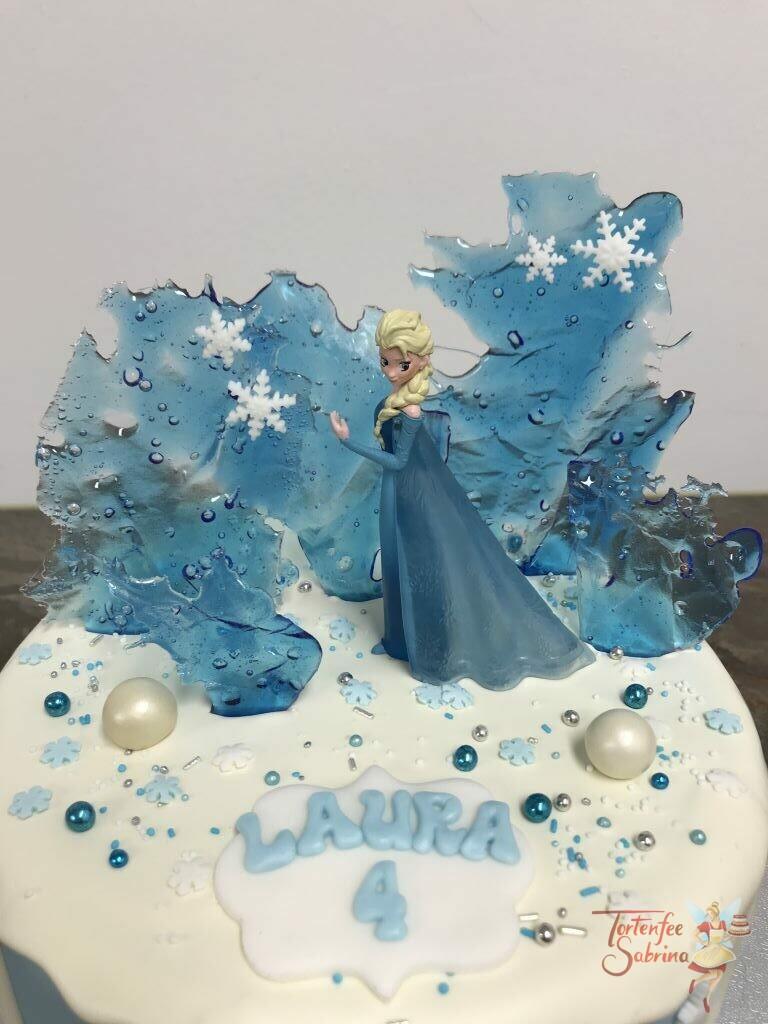 Geburtstagstorte Mädchen - Elsa's Eiskünste, hier wurden aus Zucker Eisstücke erschaffen, umgeben von einem weißem Drip.