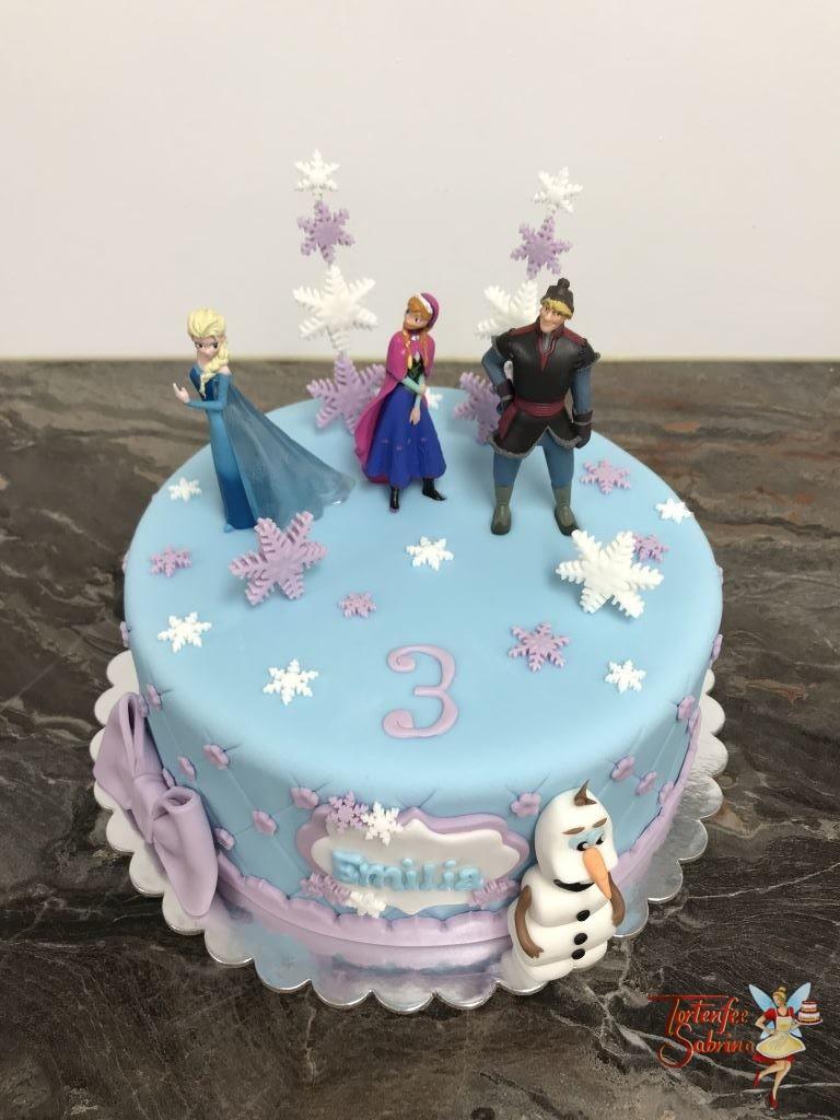 Geburtstagstorte Mädchen - Elsas Winterzauber zeigt eine blau eingedeckte Torte mit Rautenmuster und Blumen sowie einer lila Schleife und Olaf.