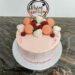 Geburtstagstorte Erwachsene - Erdbeer-Drip-Cake ist eine rosa farbene Torte mit vielen Süßigkeiten und Früchten oben drauf.