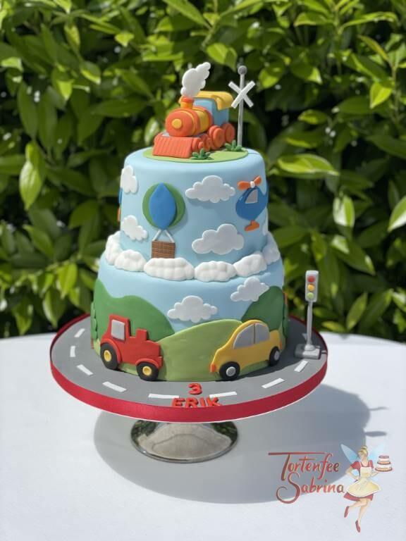 Geburtstagstorte Buben - Fahrzeuge unterwegs in der Landschaft, ebenfalls auf der Torte ein Zug, ein Auto und ein Hubschrauber.