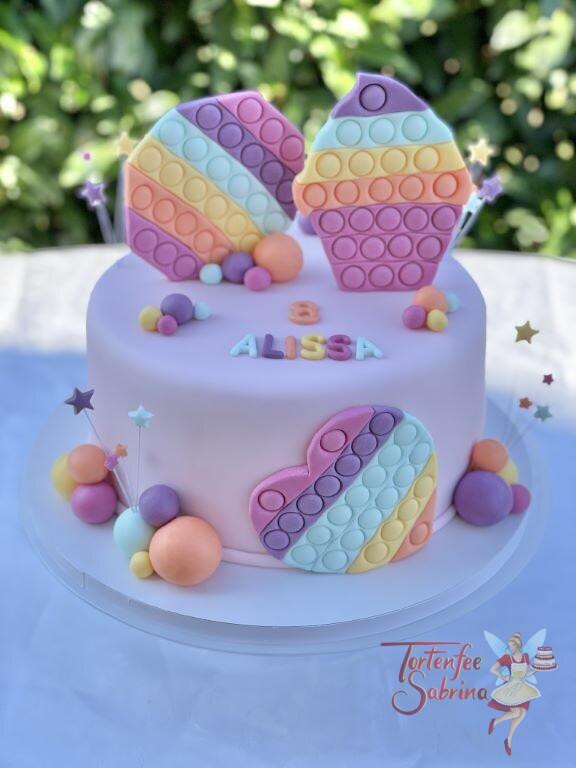 Geburtstagstorte Mädchen - Figettoys in vielen Farben zieren die rosa eingedeckte Torte, ebenso auf der Torte sind bunte Sterne.