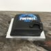 Geburtstagstorte Buben - Fortnite Playstation. Die Torte in der Form der Playstation wurde mit dem Logo von Fortnite und einem Controller verziert.