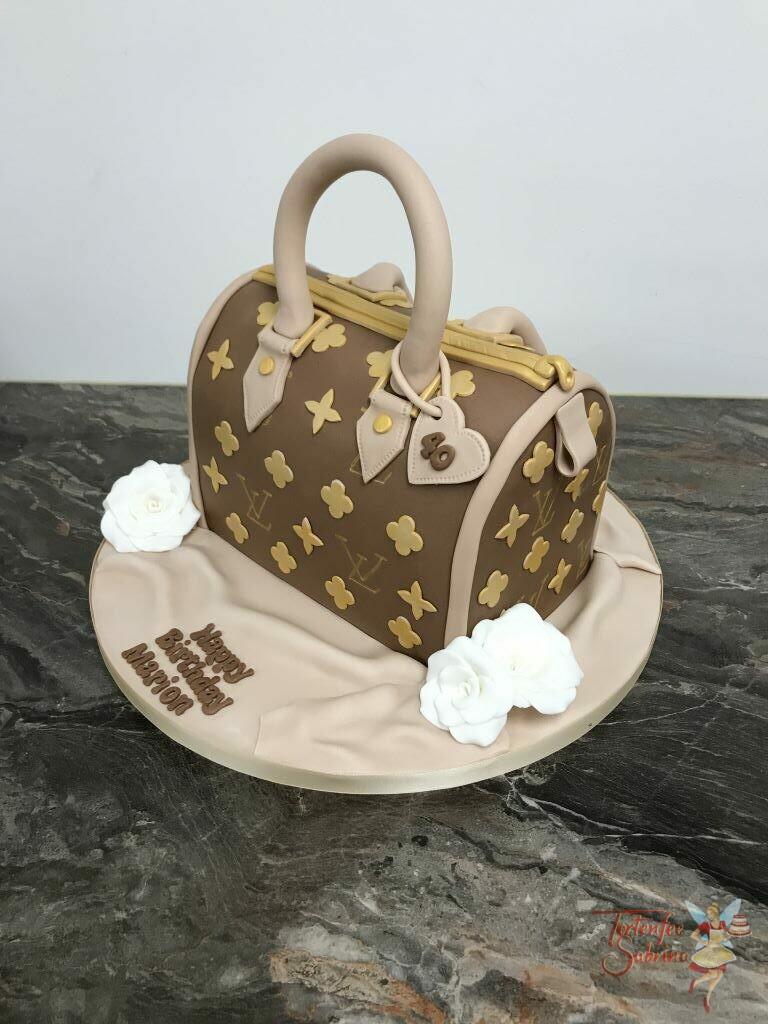 Geburtstagstorte Erwachsene - Gold-braune Tasche als Torte mit dem typischem goldenen Muster und Buchstaben, ebenso sind weiße Rosen neben der Tasche.