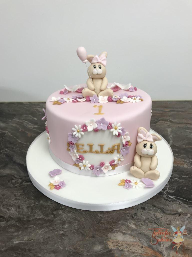 Geburtstagstorte Mädchen - Häschen auf der Blumenwiese. 2 Häschen mit rosa Schleife am Kopf und mit Luftballon.