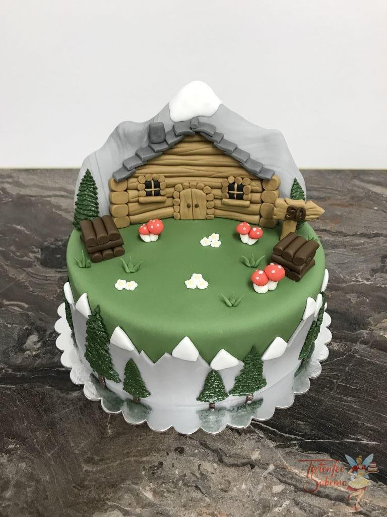 Geburtstagstorte Erwachsene - Hütte in den Bergen. Die Torte stellt eine Wiese mit einer Hütte dar, im Hintergrund ist ein schöner Gipfel.