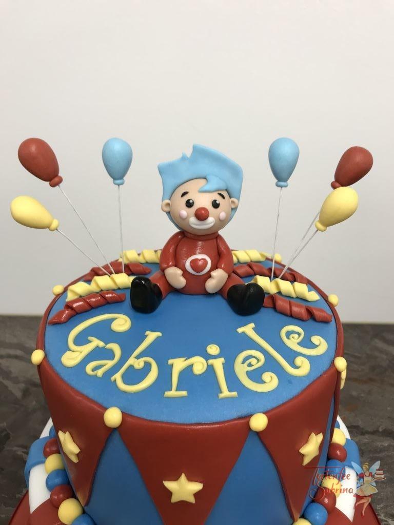 Geburtstagstorte Mädchen - Kleiner roter Clown sitzt auf der Torte die das Muster eines Zirkuszelts hat. Luftballons, Sterne und Lufschlangen sind auch auf der Torte.
