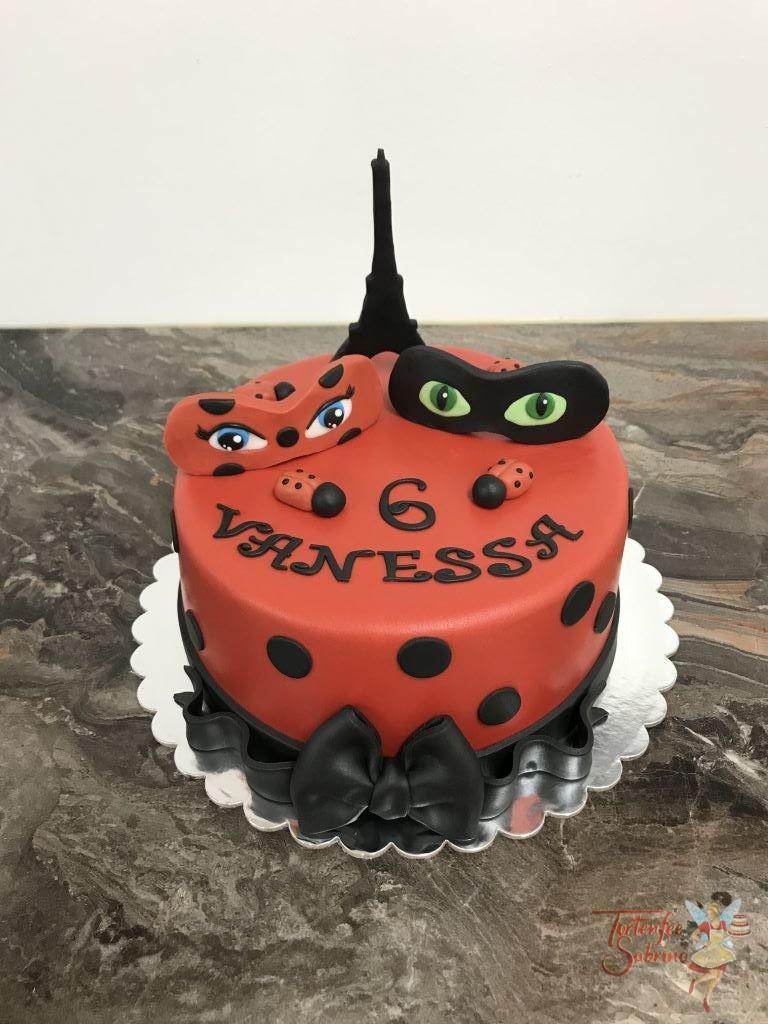 Geburtstagstorte Mädchen - Ladybug in Paris mit Eiffelturm und Masken, zum Abschluß wurde eine schwarze Schleife angebracht.