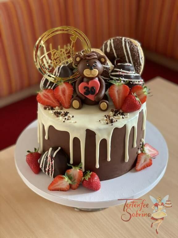Geburtstagstorte Erwachsene - Marzipanbärchen auf dem Drip Cake welcher mit Süßigkeiten, Früchten und einem Cake-Topper verziert ist.
