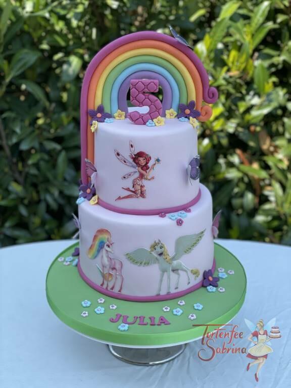 Geburtstagstorte Mädchen - Mia and me mit einem bunten Regenbogen, Blumen und Schmetterlingen, die Torte wurde zart rosa eingedeckt.