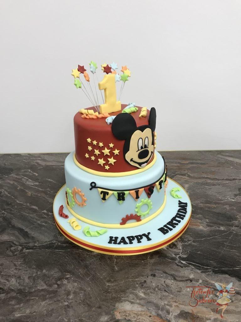 Geburtstagstorte Buben - Mickey Mouse and Stars. Die Torte ist verziert mit Sternen und Zahnrädern in den Farben rot, blau, orange und grün.