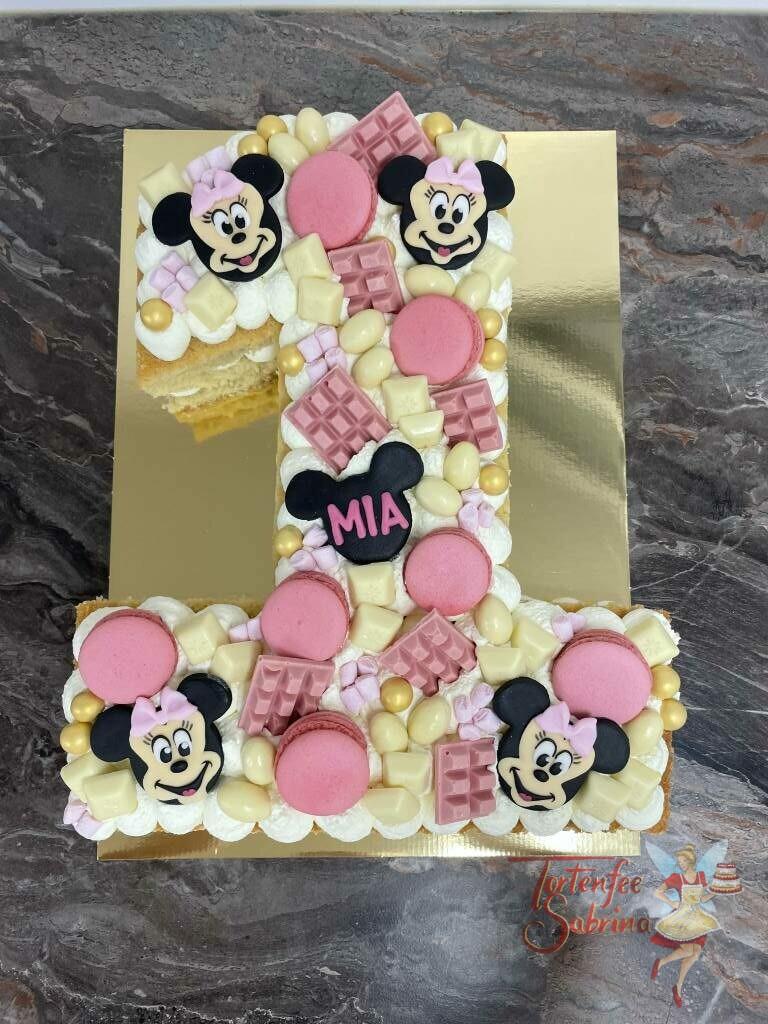 Geburtstagstorte Mädchen - Minnie Mouse auf der 1, verziert mit vielen verschiedenen Süßigkeiten und Macronen, sowie Minnie Mouse Gesichter.