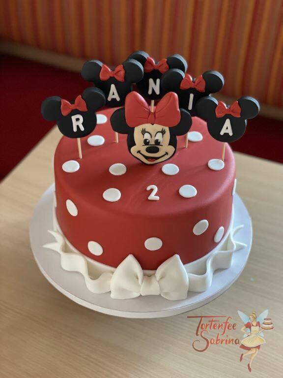 Geburtstagstorte Mädchen - Minnie Mouse mit roter Schleife, sie ziert die rote Torte welche mit weißen Punkten dekoriert ist.