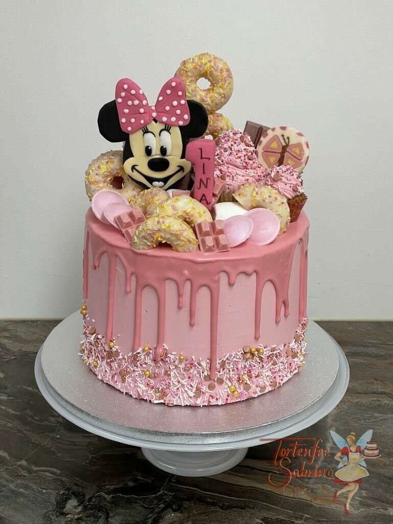 Geburtstagstorte Mädchen - Minnie Mouse zwischen Süßem wie Dounts, Schokolade und Schleckern. Die Torte wurde mit einem rosa Drip verziert.