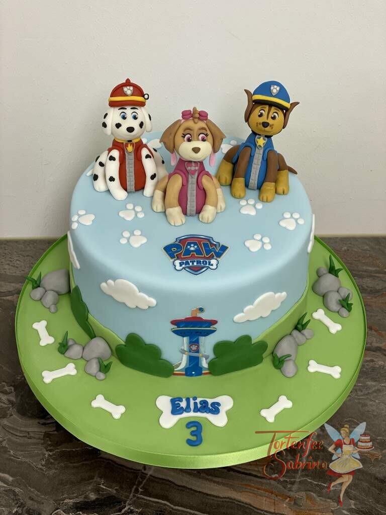 Geburtstagstorte Buben - Paw Patrol zu dritt, auf der Torte sitzen die Skye, Marshall und Chase. Ebenfalls auf der Torte ist das Logo der Paw Patrol.