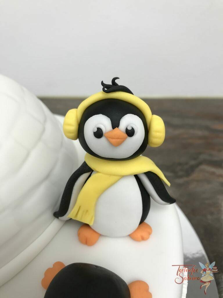 Geburtstagstorte Mädchen - Pinguine und ihr Iglu, sie spielen vergnügt um ihr Häuschen. Alles sind gut ausgerüstet mit Schal und Ohrenschützer.