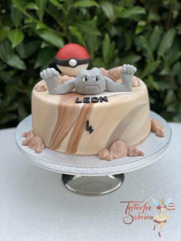 Geburtstagstorte Buben - Pokemon Kleinstein mit erhobenen Armen in der Wüste, im Hintergrund ist noch der Pokeball.