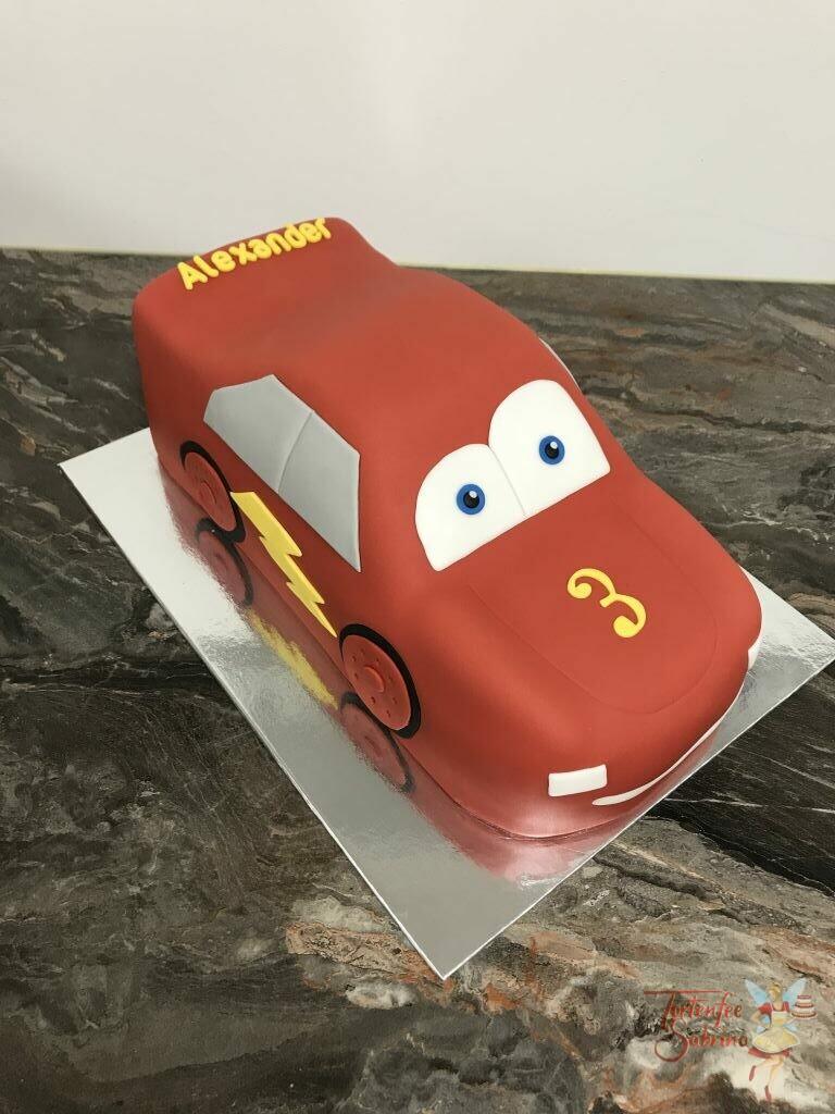 Geburtstagstorte Buben - Red Lightning McQueen, steht und glänz in seiner schönen roten Farben mit gelbem Blitz.