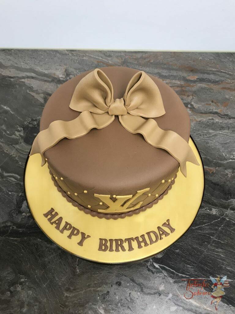 Geburtstagstorte Erwachsene - Runde Tasche hier ist das Logo in Gold gehalten und die Torte wurde oben mit einer braunen Schleife verziert.
