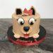 Geburtstagstorte Mädchen - Runder Hund, diese Torte wurde als Hundekopf verziert und schaut süß mit seinen großen Augen und der roten Schleife.
