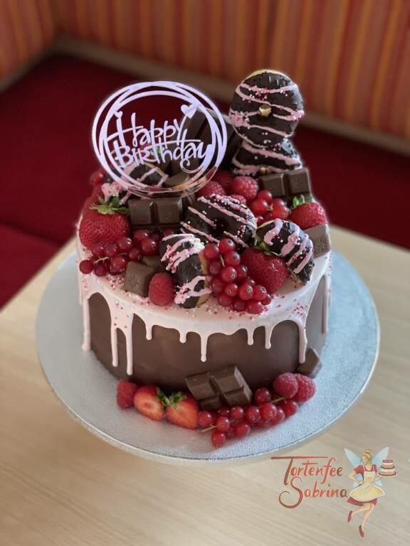 Geburtstagstorte Erwachsene - Schokolade und rote Früchte sind auf diesem Drip Cake in der Farbe rosa mit bunten Zuckerstreuseln.