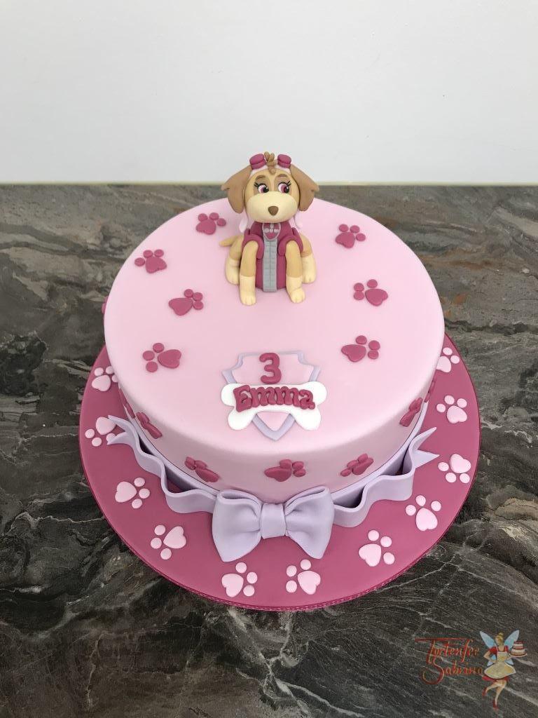 Geburtstagstorte Mädchen - Skye ganz in rosa. Hier zeigt sich der Fellfreund auf einer ganz rosa Torte mit Pfotenabdrücken und Schleife.