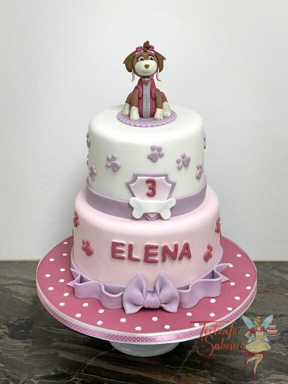 Geburtstagstorte Mädchen - Skye ganz oben auf der zweistöckigen Torte sitzend auf einem lila Deckchen und lila Schleife.