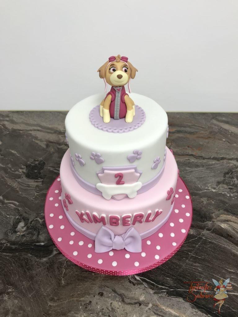 Geburtstagstorte Mädchen - Süße rosa Skye von der Paw Patrol sitz ganz oben auf der Torte, Abschluß unten ist eine Schleife.