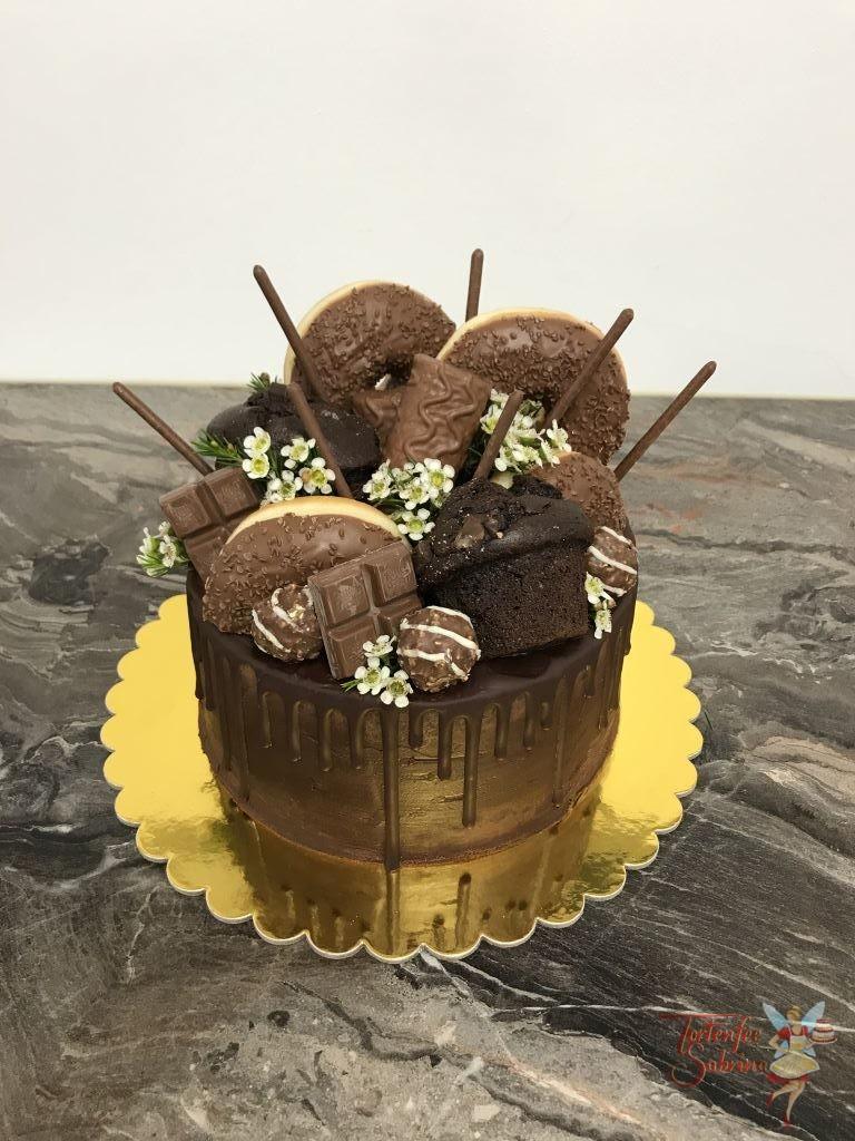 Drip Cake - Süße Überraschung, dieser Drip Cake wurde mit verschiedenen Süßigkeiten und kleine Blümchen verziert.