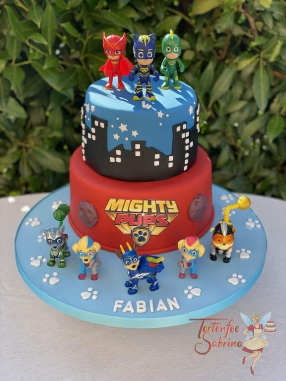Geburtstagstorte Buben - Superhelden Migthy Pubs und PJ Maske gemeinsam auf der Torte mit dunklen Gebäudesilhouetten.