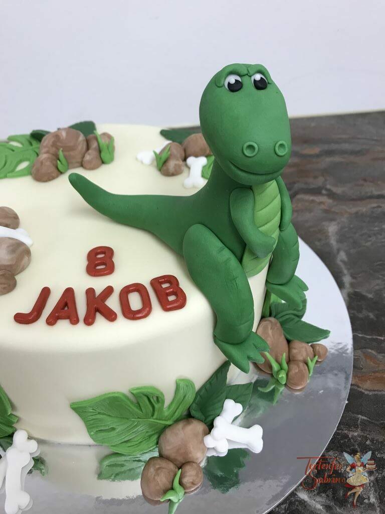 Geburtstagstorte Buben - T-Rex ruht sich aus auf der Torte und macht es sich gemütlich zwischen Blättern, Knochen und Steinen.