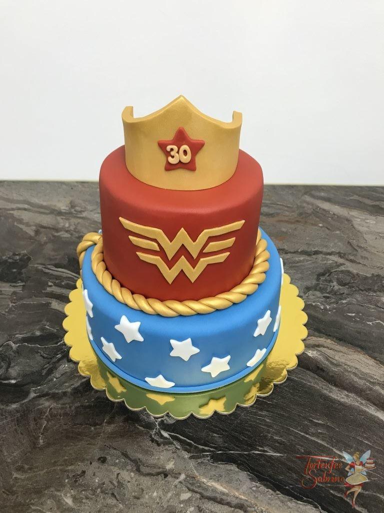 Geburtstagstorte Erwachsene - Wonderwoman mit Korne, Kordel und Schriftzug in gold. Der untere Teil der Torte ist blau mit Sternen.