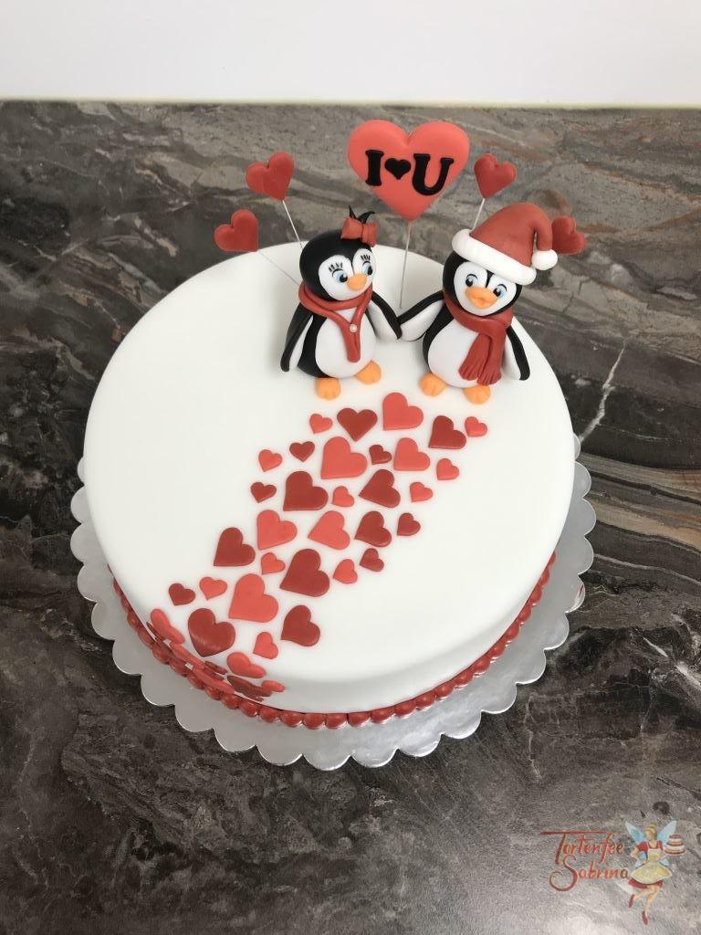 Hochzeitstagstorte - Pinguinspärchen, 2 Pinguine Hand in Hand verziert mit Schal, Haube und Schleife auf einem Weg aus Herzen in rot.