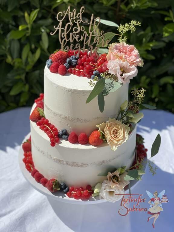 Hochzeitstorte - And the Adventure begins steht auf dem persönlichen Cake Topper, die Torte wurde noch mit Früchten und Blumen verziert.